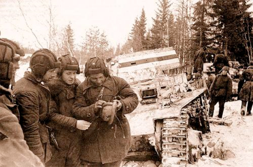 Soviet tankers inspecting some of the 6 Vickers tanks that Finns lost in the Battle of Honkaniemi, the only tank battle of the Winter War. February 1940.